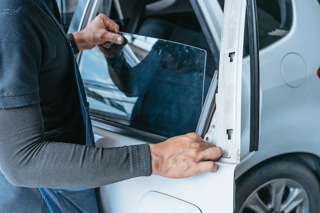 自動車修理店で白い車の壊れたフロントガラスや自動車のフロントガラスやフロントガラスの交換を変更する力学男