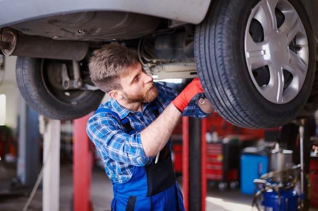 Механики, ремонтирующие автомобиль в мастерской