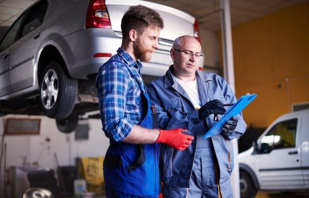 Meccanici che riparano un'auto in officina