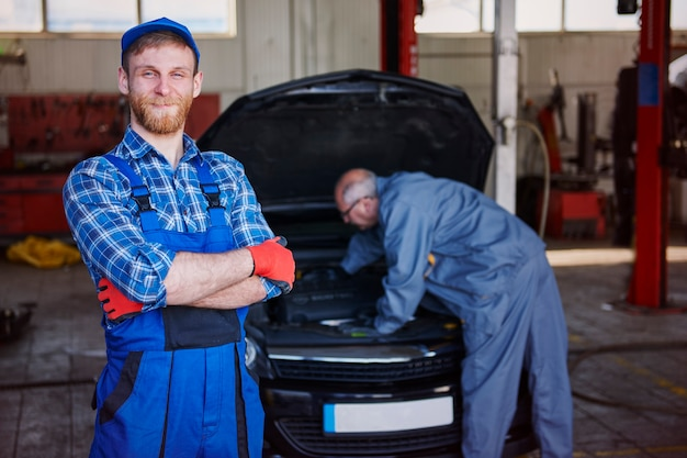 Mechanics repairing a car in workshop