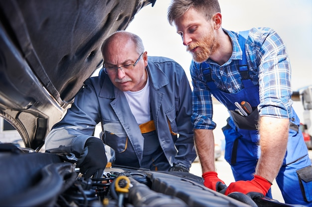 Mechanics repairing a car in the workshop