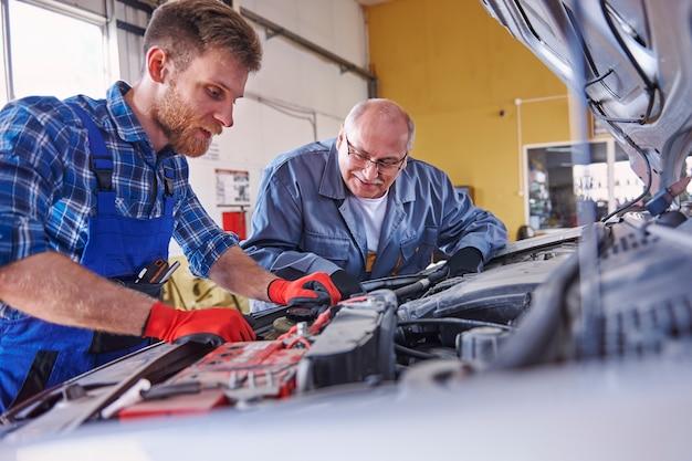 Mechanics repairing a car in the workshop
