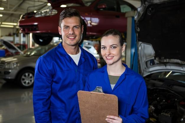 Mechanics standing with clipboard