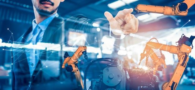 Механизированная роботизированная рука и заводской рабочий с двойной экспозицией