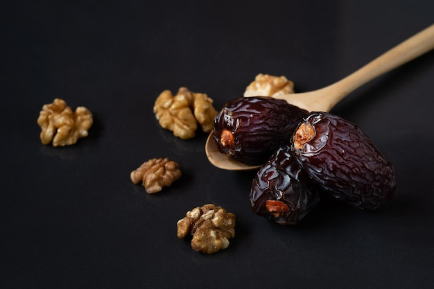 Med jool dates fruits in wooden spoon and walnuts on black background