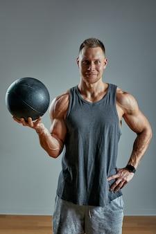 強い男がmedボールで運動をしています。灰色の背景に男の完璧な体格の写真。強さと動機。