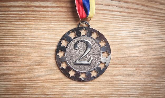Medal awards for winner on wooden table.