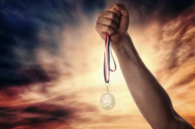 Медаль за первое место в руке спортсмена на фоне драматического неба