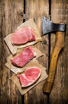 Medallions of raw meat on a tree with an axe. on wooden table. top view