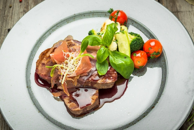 Medallions of veal, with sauce on a plate. wooden table