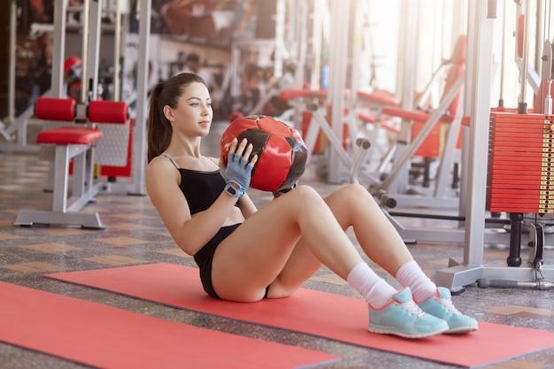 薬のボールを押しながら腹筋運動を行うヨガマットの上に座ってフィットネス女性の肖像画。 medballを運ぶとまっすぐに見てフィットネスウェアで魅力的な女性のクローズアップ。