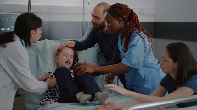 질병을 검사하는 심장 박동을 모니터링하면서 화난 어린 아이를 막으려는 의료 팀 ...