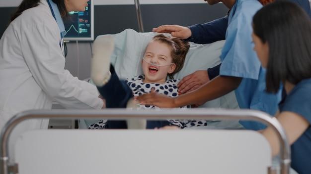酸素飽和度を監視しながら、動揺している小さな子供を止めようとしている医療チーム