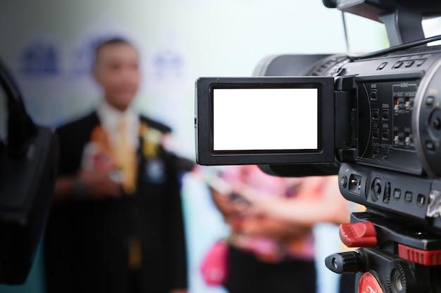 メディアインタビュー。ぼやけたvipの人とプロのビデオカメラのクローズアップ