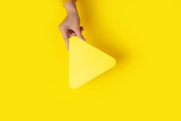 黄色の背景の上に手にメディアプレーヤーボタンアイコン