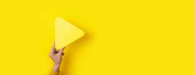 黄色の背景、パノラマのモックアップの上に手にメディアプレーヤーボタン
