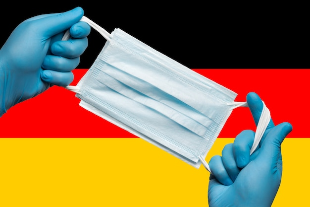 독일 국기에 파란색 장갑을 끼고 호흡용 얼굴 마스크를 손에 들고 있는 의무병. 개념 코로나 바이러스 검역, 전염병 발생 및 그립. 인간의 얼굴을 위한 의료용 호흡 붕대.