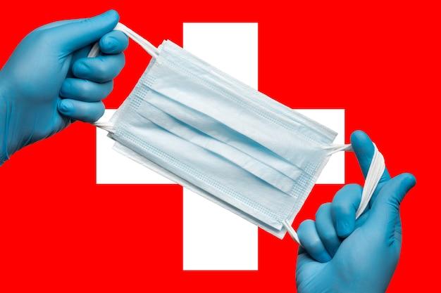 スイスの背景の旗の青い手袋で手に呼吸フェイスマスクを保持しているメディック。コンセプトコロナウイルス検疫、グリッペ、パンデミックの発生。人間の顔のための医療呼吸包帯。