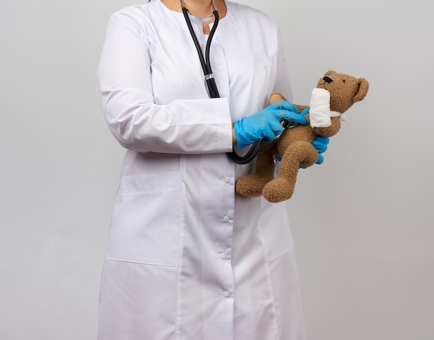 Medic holds brown teddy bear with paw bandaged in white bandage and listens to toy with stethoscope