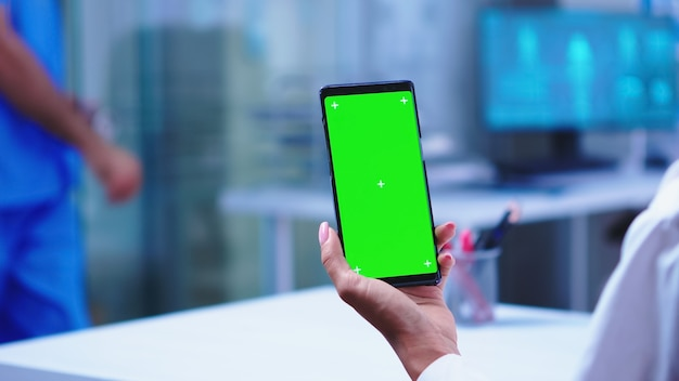 Medic in hospital cabinet holding phone with green screen wearing white coat while nurse opens glass door. healthcare specialist in hospital cabinet using smartphone with mockup.