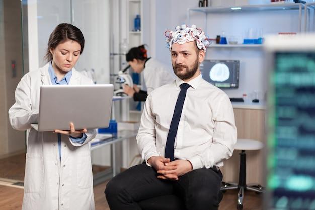 Медик-нейробиолог, работающий в неврологической исследовательской лаборатории, проводящий эксперимент над мозгом, держит ноутбук и объясняет человеку побочные эффекты нервной системы с помощью сканирующей гарнитуры.