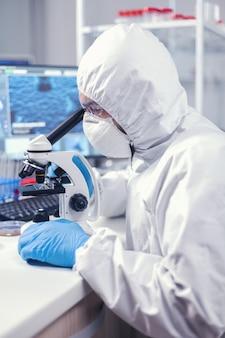 Ppeスーツに身を包んだ顕微鏡に取り組んでいる世界的大流行の時代の医者