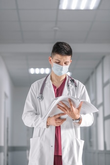 Человек-медик в маске с документами