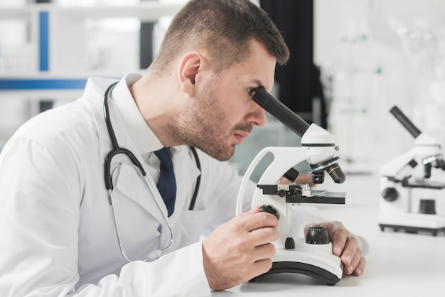 Medic man using microscope