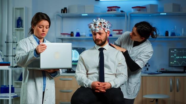 Medico in neuroscienze che lavora nel laboratorio di ricerca neurologica sviluppando un esperimento sul cervello che tiene in mano un laptop spiegando all'uomo gli effetti collaterali delle cuffie per la scansione delle onde cerebrali del trattamento del sistema nervoso