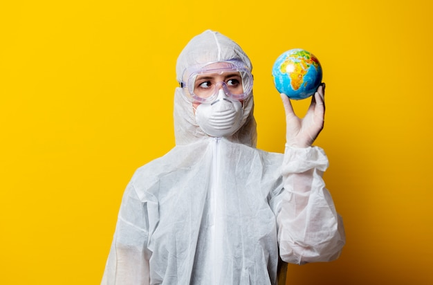 Medic in protection suit and mask hold earth globe