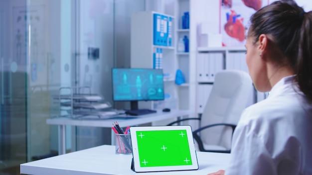 위생병은 위험한 바이러스에 대해 병원 캐비닛에 녹색 화면이 있는 태블릿 pc를 읽고 있습니다. 파란색 의료 제복을 입은 조수. 교체 가능한 화면이 있는 태블릿 컴퓨터에서 작업하는 건강 클리닉의 의사