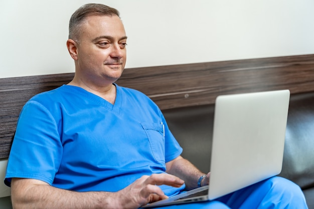 Medic in scrubs on sofa with laptop. reading documents from screen.