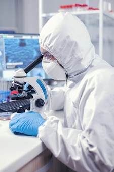 Medic in time of global pandemic working on microscope dressed in ppe suit