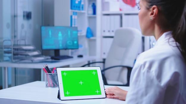 병원 캐비닛 연구를 위해 크로마 키가 있는 태블릿 pc를 사용하는 메딕. 파란색 의료 제복을 입은 간호사가 진료소에 입장합니다. 교체 가능한 스크린으로 태블릿 컴퓨터에서 작업하는 건강 클리닉의 의사