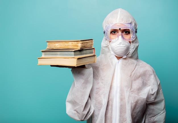 Медик женщина в защитной одежде от вируса держит книги
