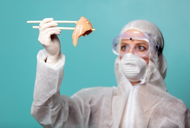 Medic woman wearing protective clothing against the virus holds raw meat with chinese chopsticks