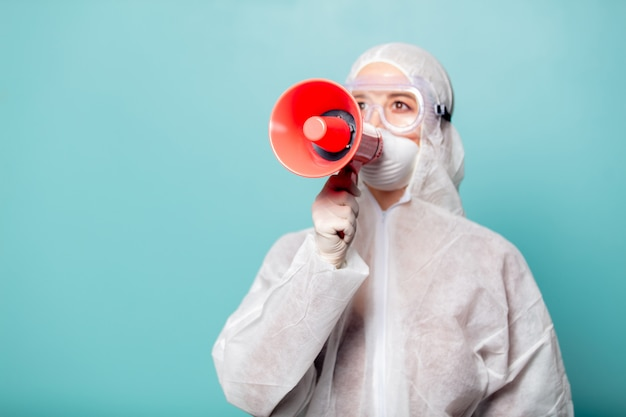 Medic woman wearing protective clothing against the virus with megaphone