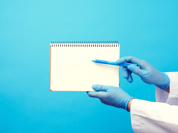 Medic woman in white coat, blue latex gloves holding an open notebook with blank white sheets