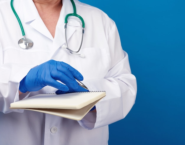 Medic woman in white coat, blue latex gloves holding an open notebook with white sheets