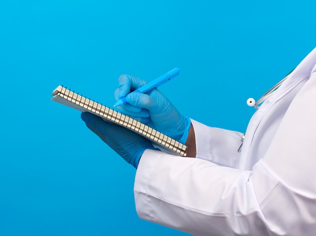 Medic woman in white coat, blue latex gloves holding an open notebook