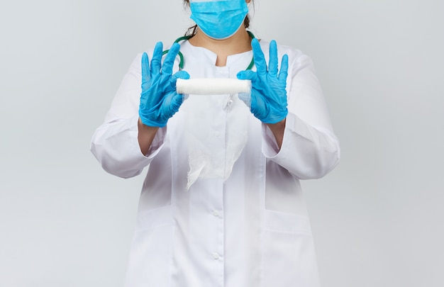 Medic woman in white coat and mask holds a twisted gauze bandage for dressing wounds
