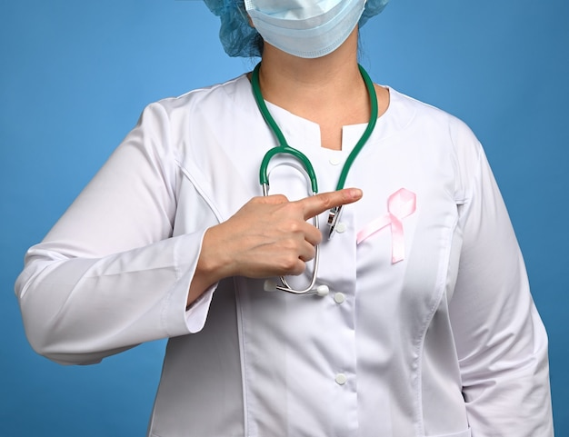 Medic woman in white coat, pink ribbon pinned to the robe, symbol of the fight against breast cancer in october , close up