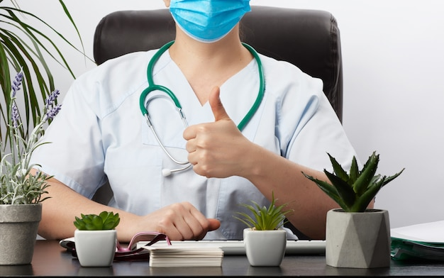 Medic woman in white coat showing like gesture in hand, approval concept