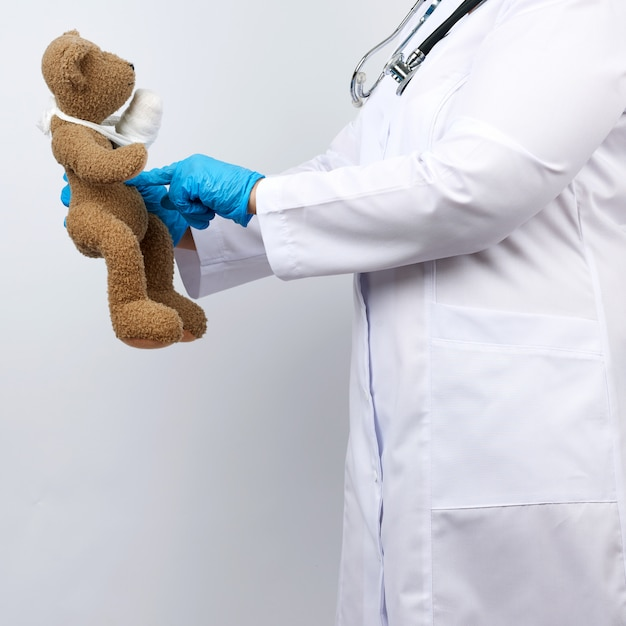 Medic woman in white coat with buttons holding a brown teddy bear with a white gauze bandage tied with her paw