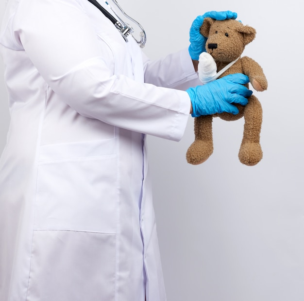 Medic woman in white coat with buttons holding a brown teddy bear with a white gauze bandage tied with her paw,