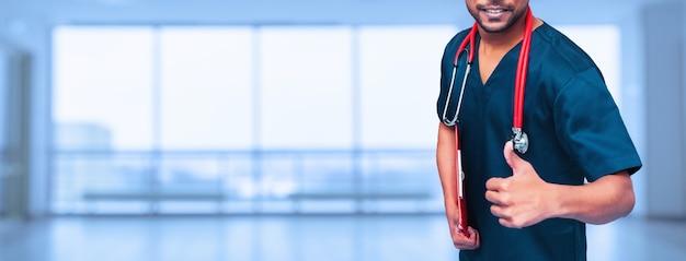 医療広告のデザイン。医学、人々、ヘルスケアの概念-青い背景の上に聴診器でアジアの男性医師の親指のクローズアップ。プロモーションバナー