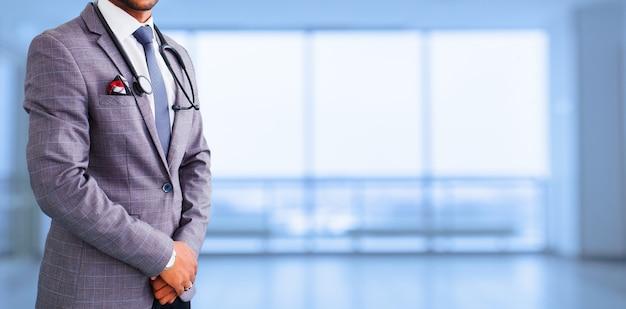 医療広告のデザイン。医学、人々、ヘルスケアの概念-青い背景の上の聴診器を持つアジアの男性医師のクローズアップ。プロモーションバナー