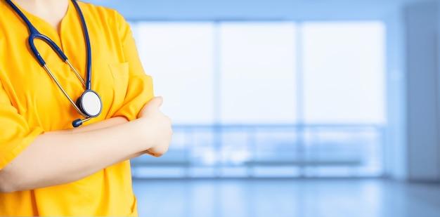 医療広告。聴診器と腕を組んで病院の黄色いコートを着た若い美しい少女。非人称的な広い背景。