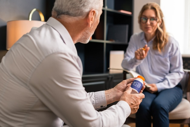 Medical advice. middle-aged caucasian blonde woman in eyeglasses having a conversation with her psychoanalyst while sitting in his office