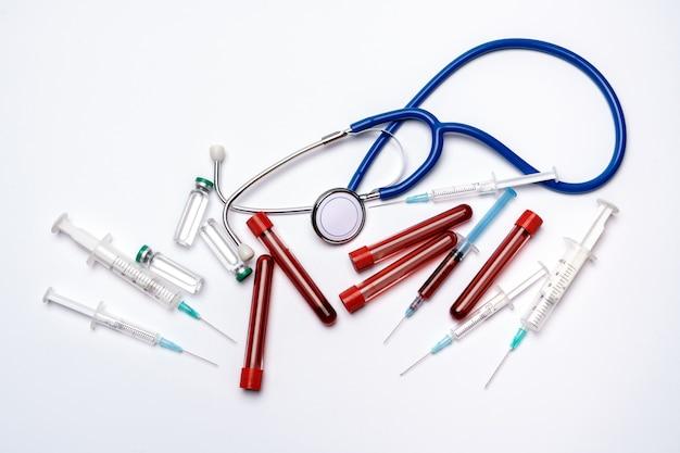 밝은 회색 또는 흰색 배경 위에 의료 앰플 튜브, 테스트 튜브, 주사기 및 청진.